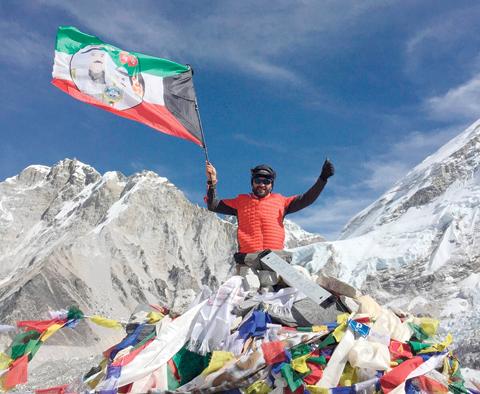 Kuwaiti mountaineer Fuad Qabazard waves the Kuwaiti flag at the Mount Everest Base Camp. - KUNA