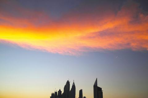 The setting sun sets wispy clouds aglow above the skyline of the Dubai Marina in Dubai yesterday. —AP