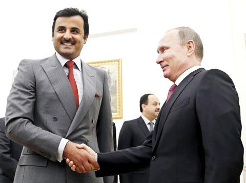 Russian President Vladimir Putin shakes hands with Qatari Emir Sheikh Tamim bin Hamad Al-Thani during a meeting at the Kremlin in Moscow