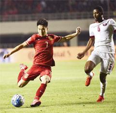 China's Wu Lei, left, fights for the ball against Qatar's Abdulaziz Hatem