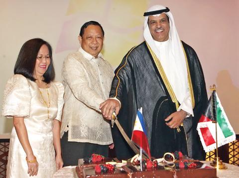 KUWAIT: Philippine Ambassador to Kuwait Renato Pedro Villa and Kuwait's Deputy Foreign Minister for Asian Affairs Ambassador Ali Al-Saeed cut the ceremonial cake