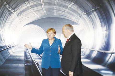 ERSTFELD, Switzerland: Swiss Federal President Johann Schneider-Ammann listens to German Chancellor Angela Merkel on the opening day of the Gotthard rail tunnel yesterday. — AP