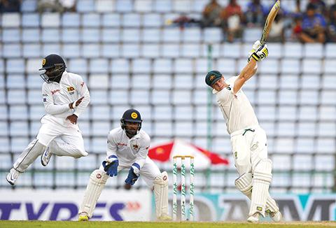 Australia's Steve Smith plays a shot as Sri Lankan fielder Kaushal Silva jumps on day four of the first test cricket match between Sri Lanka and Australia in Pallekele, Sri Lanka, Friday, July 29, 2016. (AP Photo/Eranga Jayawardena)