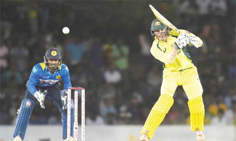DAMBULLA: Australian cricketer George Bailey (R) plays a shot as Sri Lanka's wicketkeeper Kusal Perera looks on during the fourth one day international (ODI) cricket match between Sri Lanka and Australia at The Rangiri Dambulla International Cricket Stadium in Dambulla yesterday. — AFP