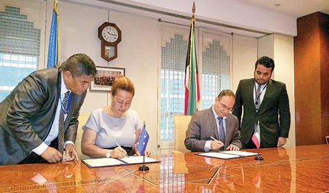 KUWAIT: UN Ambassador Mansour Al-Otaibi and United Nations Ambassador Jane J Chigiyal sign the agreement. - KUNA