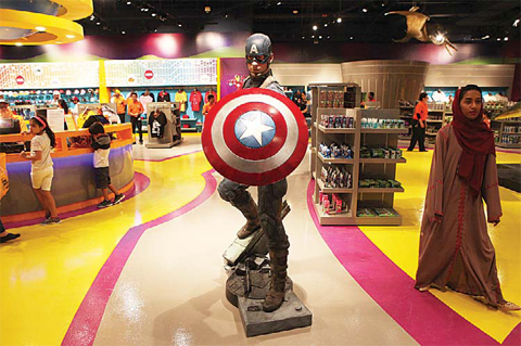 An Emirati woman walks past a statue of Captain America at the IMG Worlds of Adventure amusement park in Dubai, United Arab Emirates. —AP photos