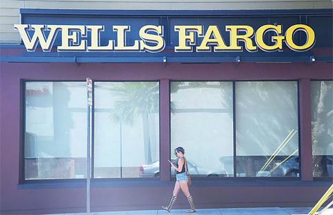 PASADENA, CALIFORNIA: A woman walks past a Wells Fargo branch on Wednesday. —AFP